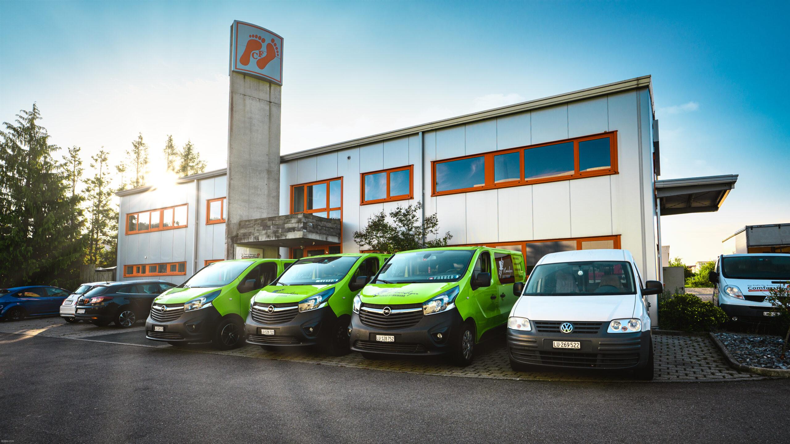 Firmenfahrzeuge vor Gebäude - Stirnimann Kaminfeger AG